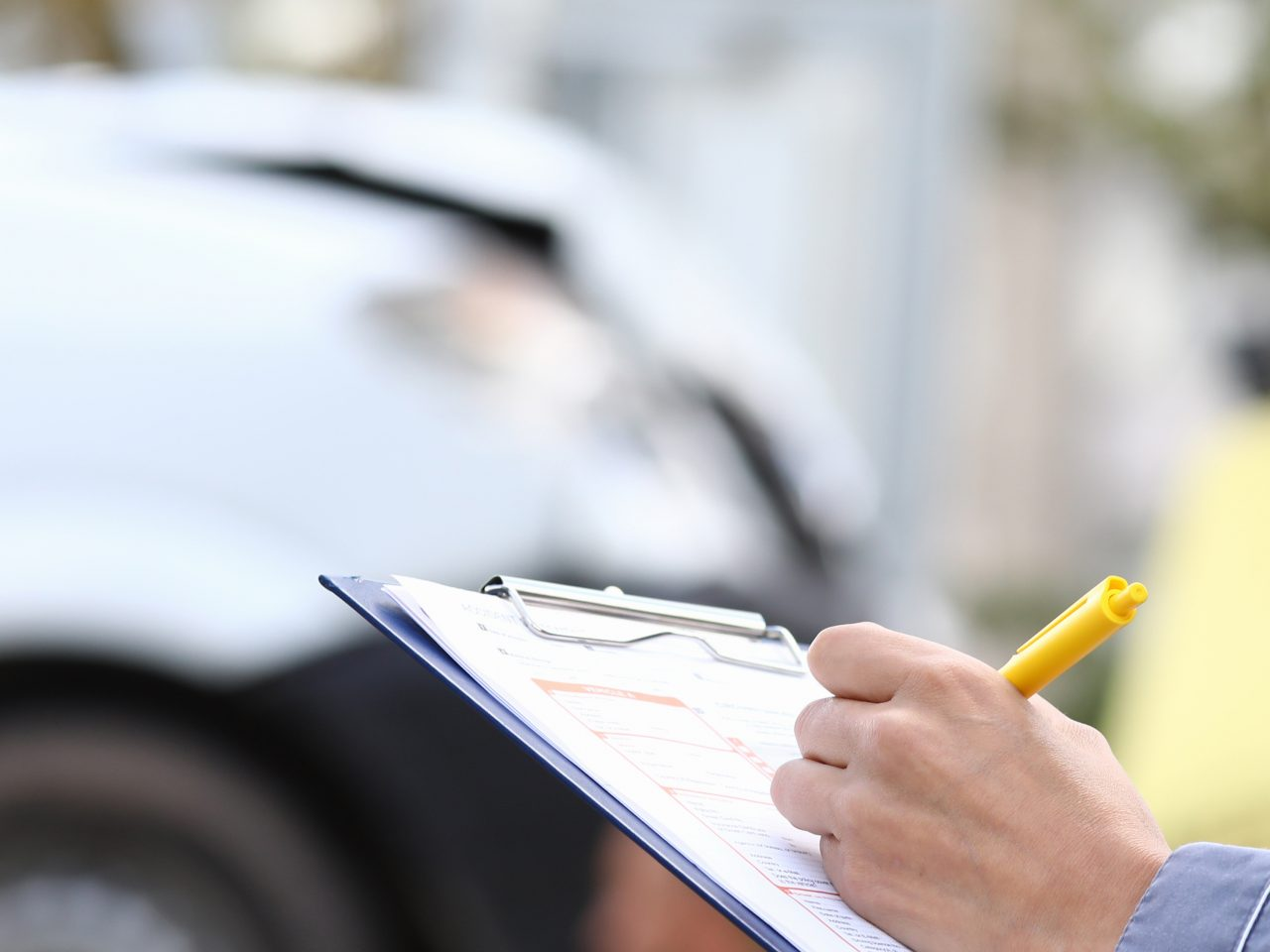 An agent fills out paperwork after car accident. Vehicle insurance concept